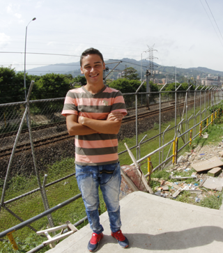 Scholarship recipient Cristian stands outside his home in Colombia.