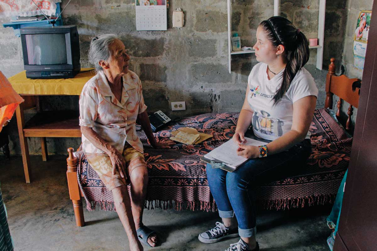 Unbound staff member and former sponsored child Yenifer visits with sponsored elder Olga in Olga's home in Tarso, Colombia.