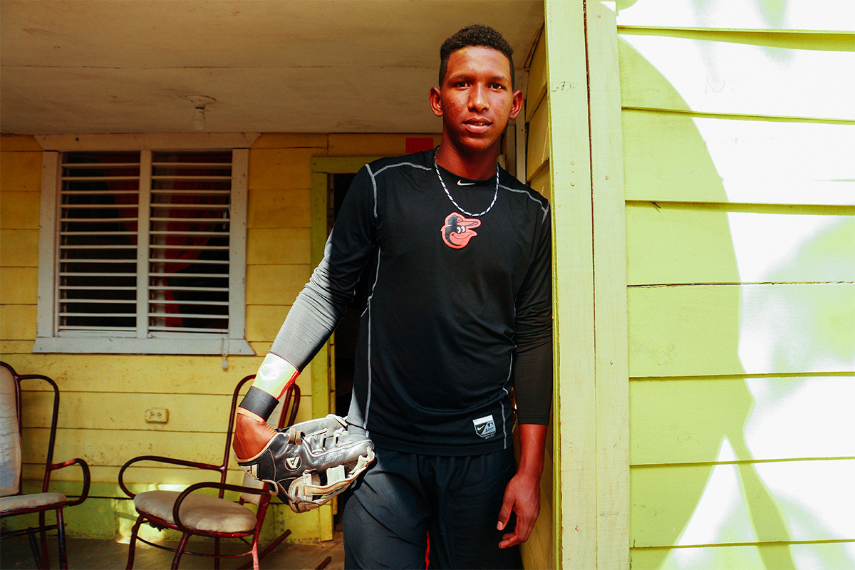 On a visit home from the Orioles' Dominican baseball facility where he trains, Damián stands on his front porch. This is the home he grew up in and where his parents and two brothers still live.