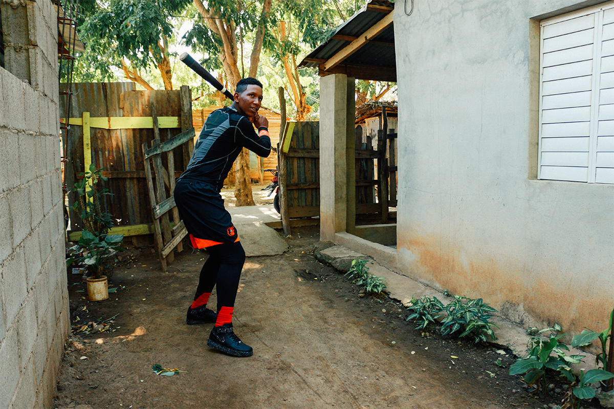 Waiting for his brother Axel to pitch him the ball, Damián practices in his yard. Like other Dominican youth, he played ball from a young age hoping for a chance at a pro career.