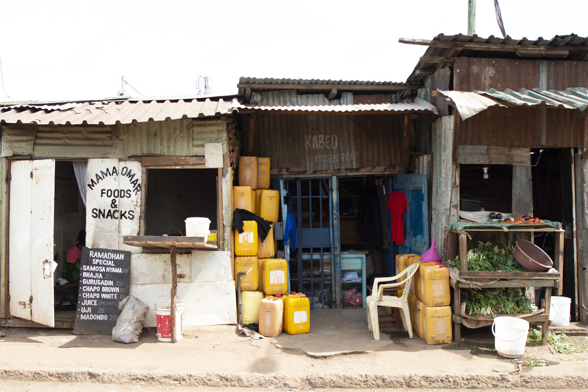 Small businesses line this street in Kibera, including the stall in the center that is owned by a family participating in the Unbound program. The business sells water and clothing made by the mother.